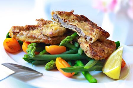Delicious Weiner Schnitzel, with asparagus, green beans, and orange cherry tomatoes.   photo