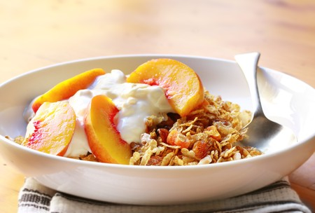 nectarine: Bowl of muesli topped with yoghurt and fresh nectarine slices.  A delicious, healthy breakfast.