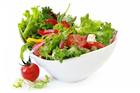 Salade du jardin en bonne santé dans l'élégant bol blanc, isolé sur blanc.