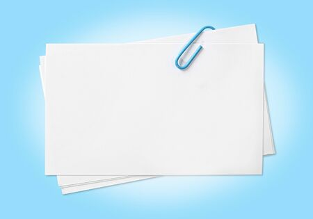 fastened: Blank white cards fastened with blue paperclip. path included. Stock Photo