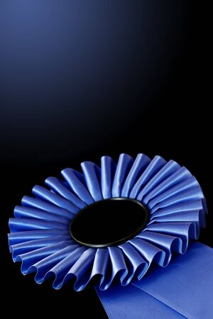first prize: Blue rosette, over black background.  Shallow DOF, lots of copy space. Stock Photo