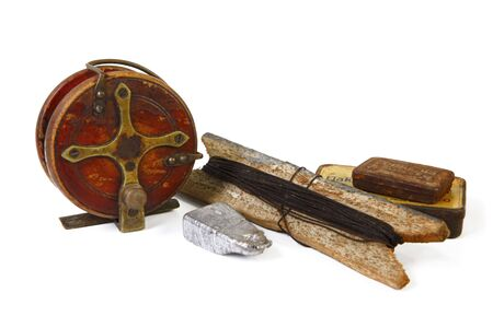 handline fishing: Vintage fishing tackle, isolated on white.  Includes wooden fishing reel, lead sinkers, rusty tin cans and a handline. Stock Photo