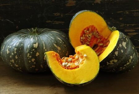 Pumpkins, whole and cut, in natural light with weathered wood background.  These are Kent pumpkins, delicious in soup. photo