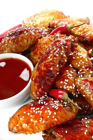 Chicken wings cooked with honey and soy, served with a chili dipping sauce and topped with sesame seeds.  Delicious sticky treat! photo