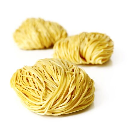 Egg noodles, isolated on white.  Focus on front