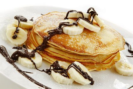 Banana pancakes with melted chocolate and powdered sugar.  A delicious indulgent dish.