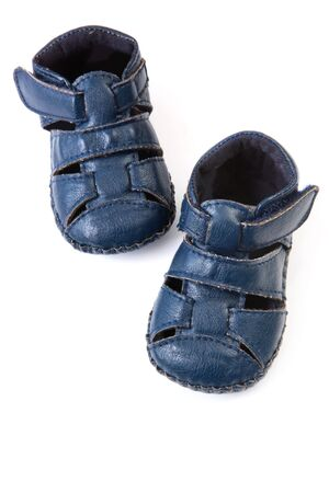 Cute little blue leather baby shoes or booties, isolated on white. photo