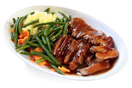 Platter of sliced roast beef with gravy, mashed potatoes, string beans and carrots.  A hearty meal. photo
