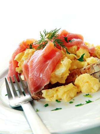 scrambled: Smoked salmon over scrambled eggs and toast, garnished with dill and parsley. Stock Photo
