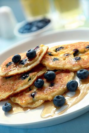 indulgent: Blueberry pancakes with maple syrup.  An indulgent sweet breakfast.