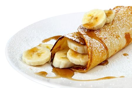 crepe: Banana pancake or crepe, with maple syrup and powdered sugar. Stock Photo