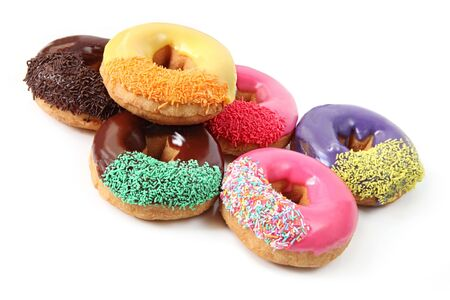 hundreds and thousands: Six iced donuts with sprinkles, isolated on white.
