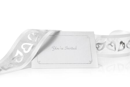 White and silver invitation, draped in ribbon with heart shapes.  Could be for a wedding, engagement or anniversary. Stock Photo - 4681074
