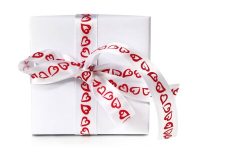 Gift box wrapped in white satin ribbon with red heart-shapes.  Isolated on white. photo