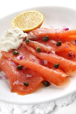 alcaparras: Aperitivo de salmón ahumado, con alcaparras, cebolla roja, limón y creme fraiche. Foto de archivo