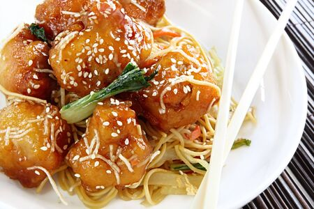Honey chicken with noodles and vegetables, topped with sesame seeds.