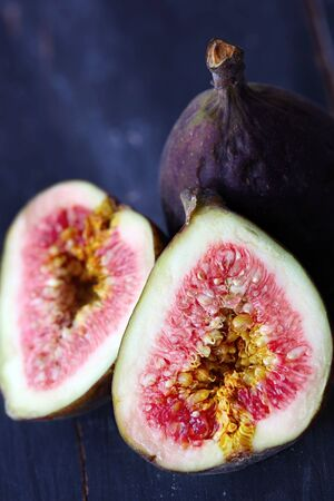 Fresh figs, cut and whole, on dark weathered timber. Stock Photo - 4706983