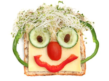 sultanas: Face on bread, made from cheese, sprouts, capsicums, tomato, cucumber and sultanas.  Healthy fun snacking. Stock Photo