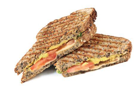aguacate: S�ndwich asado con queso, tomate y aguacate en pan de semillas. Aislado en blanco. Foto de archivo