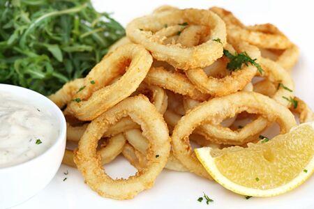 Fried calamari, with arugula salad, tartare sauce, and lemon. photo