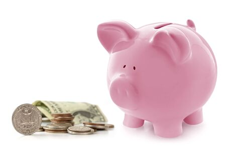 Pink piggy bank with US coins and notes.  Isolated on white.