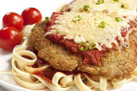 Chicken parmesan or parmigiana, with melting mozzarella and parmesan cheeses, over fettucine ribbon pasta. Stock Photo