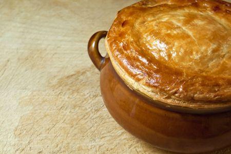 まな板: 古い木製のまな板、オーブンからまっすぐに鶏鍋のパイ。 黄金の茶色のパイ生地。