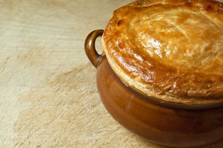 puff: Chicken pot pie on old wooden chopping board, straight from the oven.  Golden brown puff pastry. Stock Photo