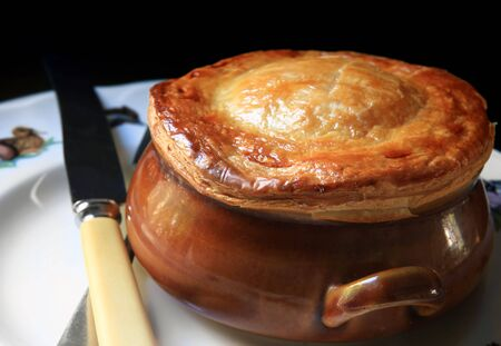browned: Chicken hot pot or pot pie, in old brown pottery ramekin, with vintage knife and fork.