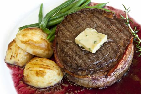Filet mignon with parsley butter and a red wine jus, served with roasted potatoes and green beans. photo