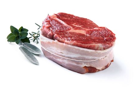 uncooked bacon: Filet mignon.  Best beef steak wrapped in bacon, ready for cooking.  With fresh sage, oregano and rosemary, isolated on white.