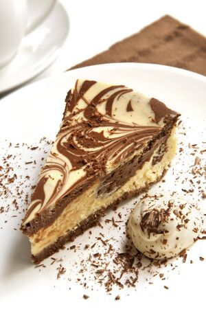 marbled: Chocolate marble cheesecake with cream and shaved chocolate, and a cup of coffee.