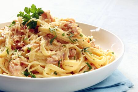 carbonara: Fettucine carbonara in a white bowl, garnished with parmesan and parsley. Stock Photo