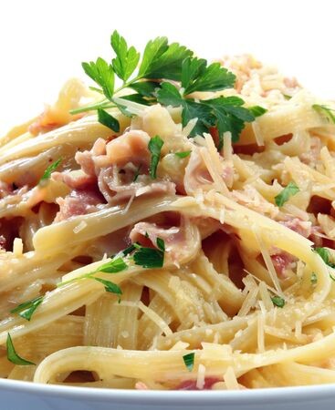 carbonara: Fettucine carbonara in a white bowl, garnished with parmesan and parsley.  Delicious creamy sauce.