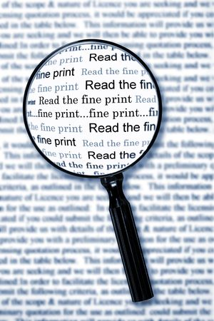 Magnifying glass over document, highlighting the words read the fine print.  Cyan toned image. photo
