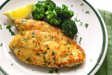 breaded: Breaded and herbed chicken fillet, served with broccoli and lemon. Delicious chicken schnitzel.