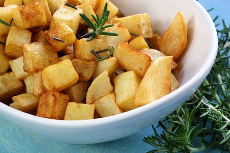 cubed: Potatoes roasted with rosemary, in stylish white bowl.