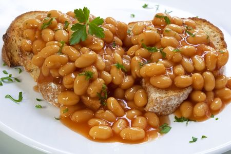 Baked beans on sourdough toast, garnished with parsley. photo