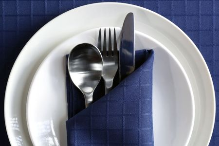 Place setting with plates, silverware, and navy blue napery. photo