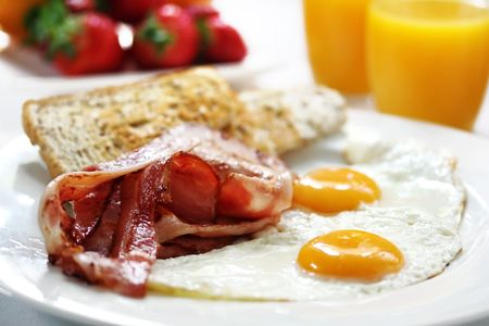 Bacon and eggs with toast, orange juice and fresh fruit.  Shallow DOF.