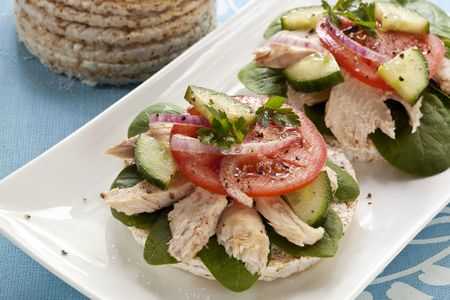 red onion: Rice crackers with white flaked tuna, baby spinach, tomato, cucumber and red onion.  Healthy eating! Stock Photo