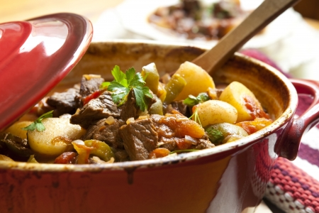 goulash: Traditional goulash or beef stew, in red crock pot, ready to serve.  Shallow DOF.