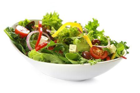 Estilo griego en ensalada tazón blanco, aislados en blanco. Bonito queso de cabra, aceitunas Kalamata, tomates cherry, cebolla roja, pimientos y lechugas mixtas. Foto de archivo
