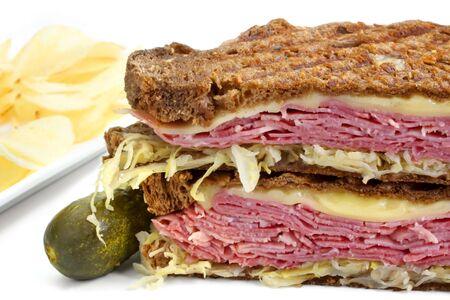 reuben: Reuben sandwich, with pastrami, sauerkraut, melting Swiss cheese on dark rye bread.  With dill pickle and potato crisps.