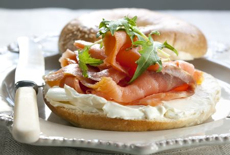 shallow dof: Bagel with smoked salmon and cream cheese, topped with rocket (arugula).  Shallow DOF. Stock Photo