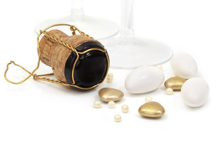wedding favors: Champagne cork, with wedding favors or bonbonniere.  Sugared almonds, gold heart-shapes, and cachous.  Champagne glasses behind.   Stock Photo