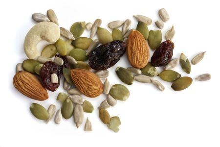 scattered on white background: Trail mix of nuts, seeds, and dried fruit.  Healthy snacking, isolated on white. Stock Photo
