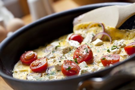 Cooking omelet in a pan, ready to serve.  With Cherry tomatoes, red onion, goats cheese and parsley.