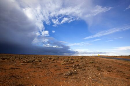 australian landscape: Storm brewing over the red earth of the Australian outback.  Western New South Wales, near Broken Hill.