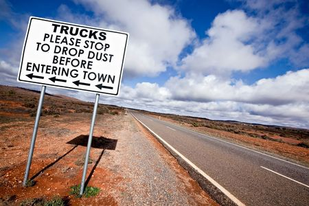 broken hill: Road sign in the Australian outback, asking trucks to stop to drop dust before entering town.  Outside Broken Hill, in western New South Wales.